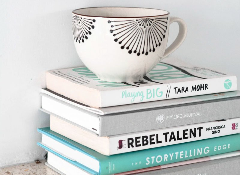 A cup of tea rests on a pile of books