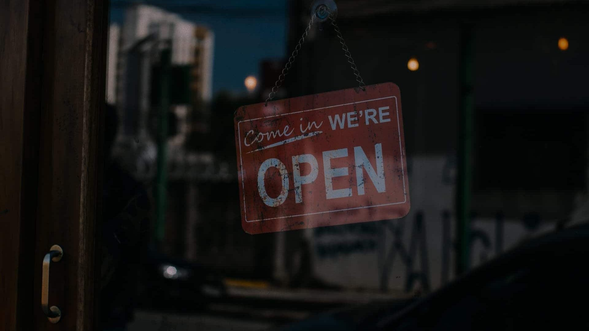 A sign hanging in a door reads Come In We're Open