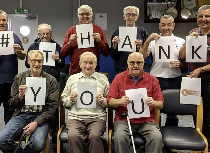 An elders community group hold up thank you signs